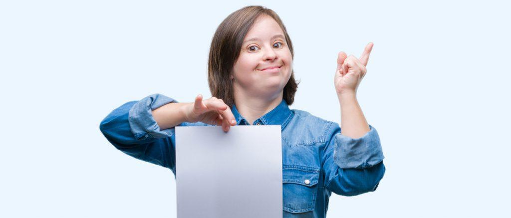 患有唐氏综合症的年轻成年女性在孤立的背景上拿着空白纸,非常高兴地用手和手指指着一边